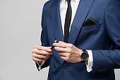 close-up photo of young businessman wearing suit holding pen