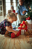 girl open present in front of a decorated Christmas tree