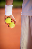 Tennis balls and racket on red dross