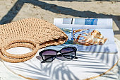 Straw bag and sunglasses with a seashell and a magazine on a white background. Summer holiday scene. Women's things