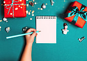 Child writting a letter to Santa. Christmas gift boxes on blue frozen background.
