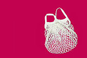 Empty eco bag isolated on a bright pink background