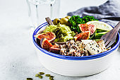 Buddha bowl with quinoa, tofu, kale, fig and guacamole hummus in a white plate.