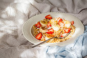 Oatmeal with banana, strawberries and peanut butter in white plate in bed backgrond.