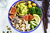 Buddha bowl with quinoa, tofu, kale, fig and guacamole hummus in a white plate, top view.