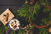 Christmas composition on dark background. Christmas wreath, cocoa, gift box and christmas decoration background.
