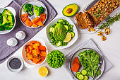 Healthy vegan food lunch, top view. Green salad, sweet potato, vegan cake, vegetables on white background.