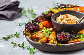 Baked vegetables with hummus in a dark dish.