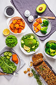 Healthy vegan food dinner table, top view. Green salad, sweet potato, vegan cake, vegetables on white background.