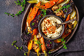 Baked vegetables with hummus in a dark dish, top view.