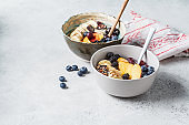 Oatmeal with banana, peach, berries and superfoods in bowls.