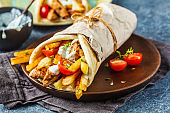 Gyros souvlaki wraps in pita bread with chicken, potatoes and tzatziki sauce.