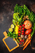 Autumn vegetables background. Pumpkin, zucchini, sweet potatoes, carrots and beets on dark background.