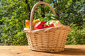 Basket with ripe vegetables on a rustic wooden table on a background of trees in the yard