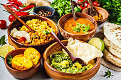 Food traditional Indian cuisine. Dal, palak paneer, curry, rice, chapati, chutney in wooden bowls on white background.