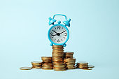 Finance investment, Time is money. Alarm clock and golden money coins, pension