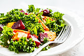 Kale salad with baked vegetables in white plate.