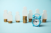 Alarm clock and golden money coins, capitalization. Time is money concept, payment