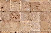 Background texture of old beige marble wall from a variety of large tiles square shaped