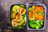 Healthy meal prep containers with green burgers, broccoli, chickpeas and salad.