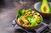 Vegan lunch in a coconut bowl: green burgers with salad and chickpeas.