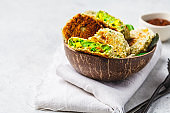 Green vegetarian burgers in coconut shell with tomato sauce on white background.