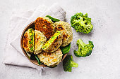 Green broccoli burgers in coconut shell dish on white background, top view.