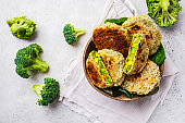 Green broccoli cutlets in coconut shell dish on white background.