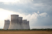 Cooling towers of the nuclear power plant against the cloudy sky. Ecology and air pollution concept.