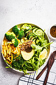 Green salad with broccoli, zucchini pasta, avocado and dressing.