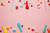 Kids birthday party decoration, pink background (pattern). Colorful candies, bright balloon, festive candles, and paper straws