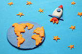 Creative craft plasticine rocket in open space, astronaut dreams. Stars, planet earth. Cartoon art