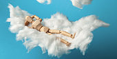 Comfortable dream of toy man on clouds, sweet dreams. Rest on bed
