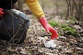 Hand of volunteer lift off litter ground. Spring cleaning in nature, outdoor trash and rubbish
