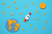 Creative craft plasticine rocket in open space, astronaut dreams. Stars, planet earth and moon. Cartoon art