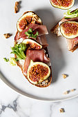 Trendy sandwiches with ham and figs on white plate and white marble patterned backgorund. Gourmet conception.