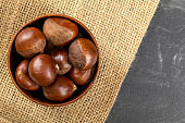 Tabletop view, small wooden bowl with chestnuts on jute cloth and slate like table