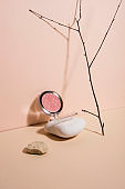 Powder blush on a spa stone, on a nude pastel background.