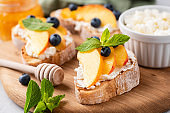 Bruschetta with fruits and soft cheese