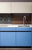 Beautiful blue kitchen unit, kitchen faucet, wooden apron in the kitchen. Modern minimalistic kitchen design