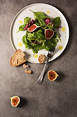 Green salad with figs on white plate and grey background.