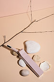 Stones on pastel background with an opened perfume. Abstract still life. Makeup collection 9.