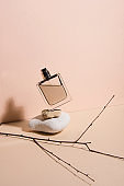 Pastel color perfume falling from the a stone . Abstract still life. Makeup collection 5.