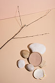 Stones on pastel background with an opened powder. Abstract still life. Makeup collection 8.
