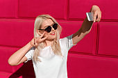 Charming casual girl taking selfie in sunlight