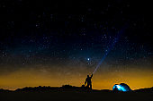 Night sky with stars and silhouette of a standing happy man with blue light. Space background - travel people concept - free camping and outdoor adventure - discover the world lifestyle