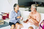 cheerful and relaxed couple of adult senior caucasian people at home sit down on a white sofa and speak together drinking a tea break. retired life concept for mature people enjoying the daily life