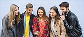 A group of people standing by the wall and takeing a selfie-  Friends enjoying online technology and shareing videos\ photos- Lifestyle concept