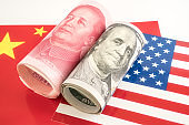 Dollar and Yuan currency lying on the flags of USA and China