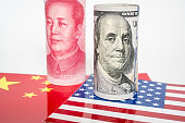 Dollar and Yuan currency standing on the flags of USA and China